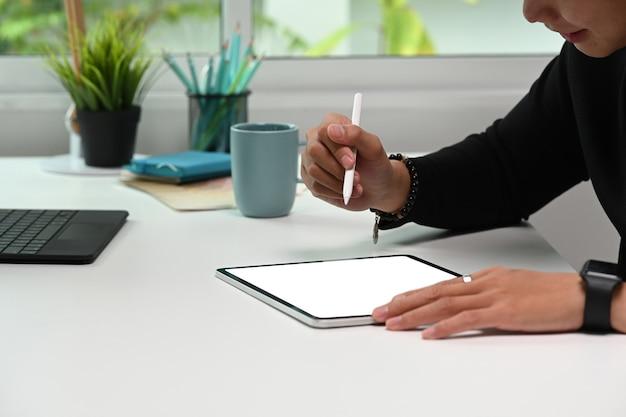 흰색 책상에 디지털 태블릿으로 일부 사진을 편집하는 그래픽 디자이너의 자른 샷.