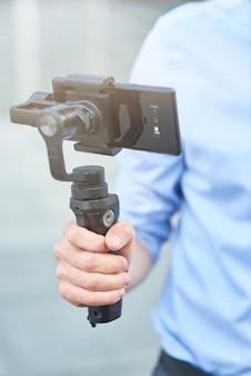 야외에서 녹음하면서 스마트폰으로 짐벌을 들고 남성 블로거의 자른 샷