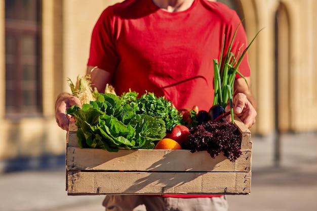 Обрезанный снимок курьера-мужчины в униформе, держащего деревянную коробку со свежими зелеными продуктами
