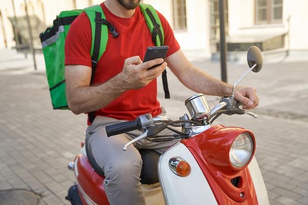 모바일 앱을 사용하여 보온 가방을 든 남성 택배의 자른 샷