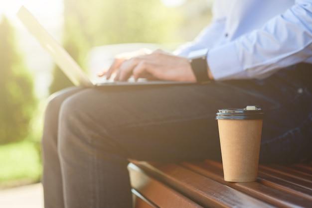 노트북으로 온라인 작업을 하고 책상에 앉아 커피를 마시는 남성 프리랜서의 자른 사진