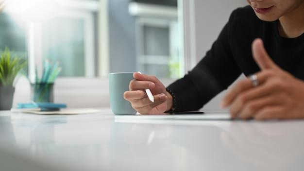 Обрезанный снимок человека, графического дизайнера, использующего графический планшет и стилус на своем рабочем месте
