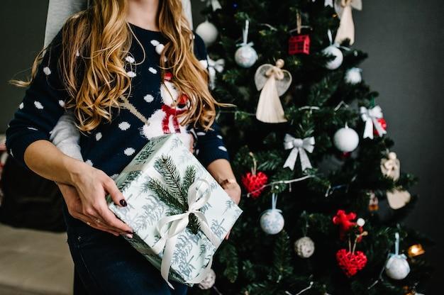 木の近くでクリスマスプレゼントを持ってガールフレンドを驚かせた男のクロップドショット。家族がプレゼントボックス、ナイトクリスマスを贈ります。メリークリスマスとハッピーホリデー!家族が贈り物を交換します。