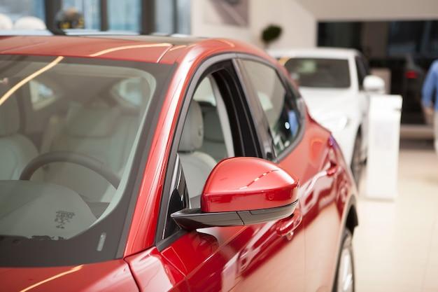 Обрезанный снимок нового блестящего красного автомобиля в продаже в автосалоне.