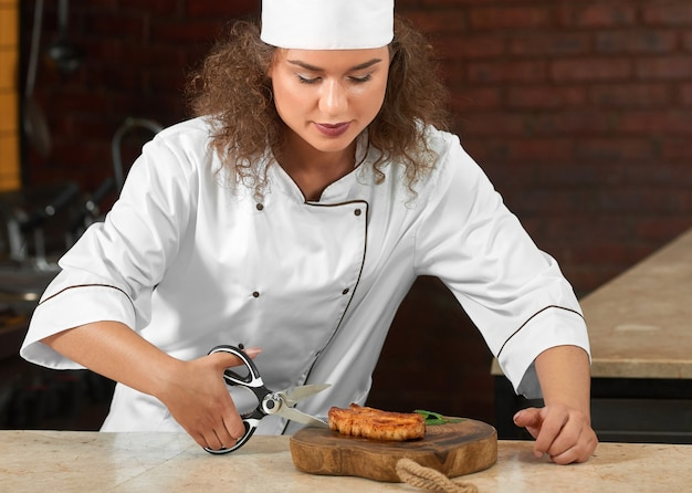 Обрезанный снимок профессионального шеф-повара, режущего ножницами мясо на гриле, работая на кухне ресторана.