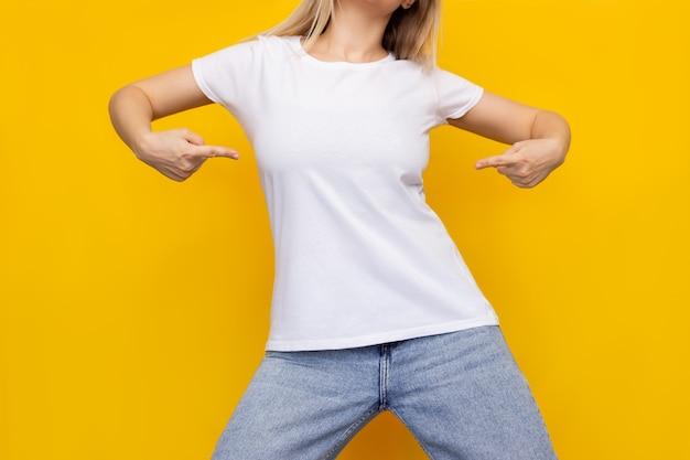明るい色の黄色い壁に空のコピー スペースを示す指で白いカジュアル t シャツを指しているデニム ジーンズの若いブロンドの女性のトリミングされたショット