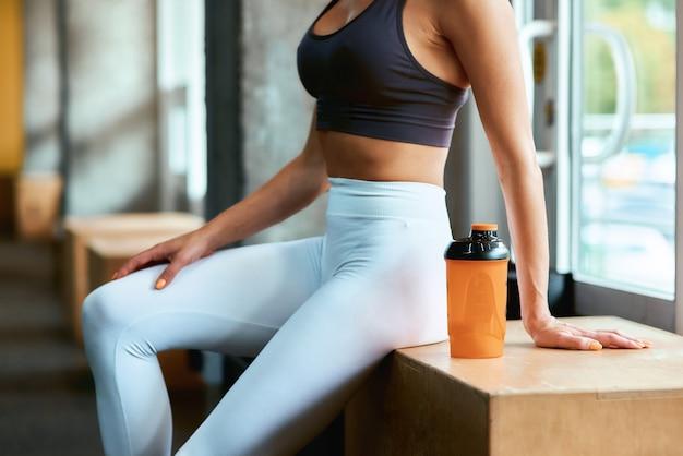 체육관에서 운동 후 쉬고 있는 운동복을 입은 젊은 피트니스 여성의 자른 샷. 낚시를 좋아하는 사람들, 훈련 및 건강한 생활 방식