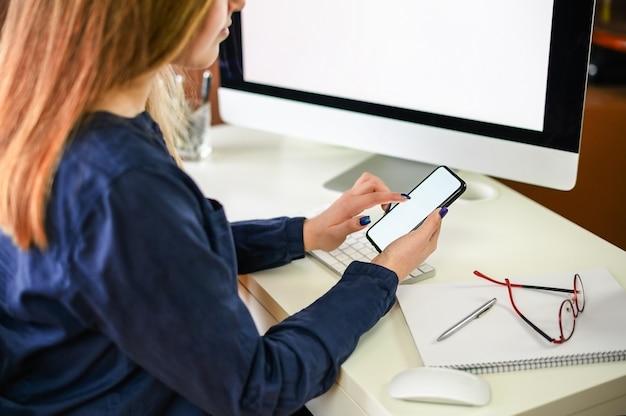 Обрезанный снимок молодой женщины, работающей из дома с помощью смартфона и компьютера, руки женщины с помощью смартфона в интерьере, женщины на домашнем рабочем месте с помощью технологии. фото высокого качества
