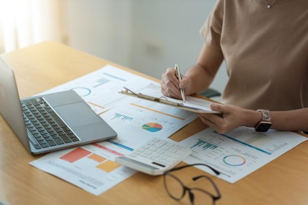 会計士のトリミングされたショットは、彼のオフィスでラップトップ上の財務報告を分析する、ビジネス分析の概念