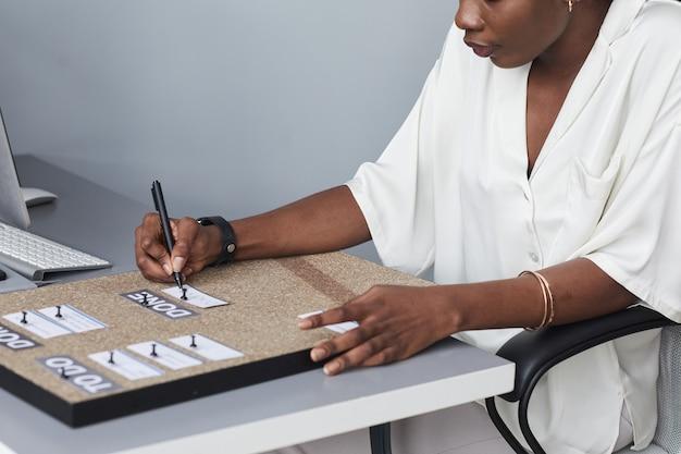オフィスのデスクで作業中にチャートを作成することを計画しているアフリカ系アメリカ人の実業家のトリミングされたショット、コピースペース