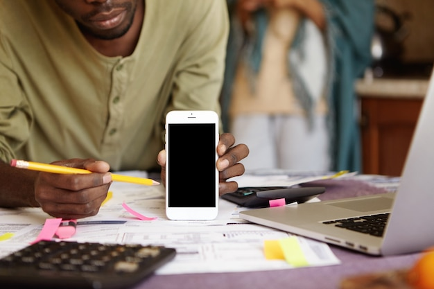 携帯電話を保持しているとその空白の画面で鉛筆を指しているアフリカ系アメリカ人の男のショットをトリミング