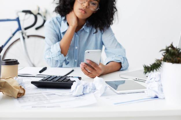 작업 테이블에 집에 앉아 아프리카 계 미국인 젊은 여성 프리랜서의 자른 샷