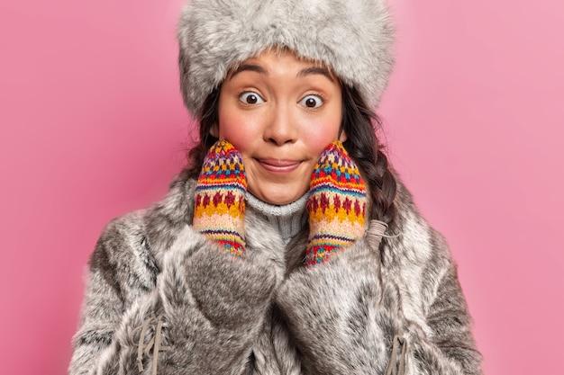 따뜻한 겉옷에 놀란 겨울 여자의 자른 샷은 놀랍게도 분홍색 벽에 얼굴 포즈에 손을 유지합니다.
