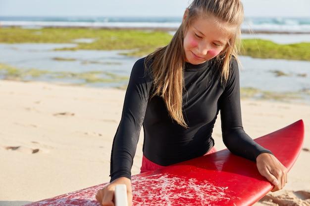 매력적인 여성의 자른 샷은 안전한 서핑을 위해 왁스를 사용하고 매력적인 외모를 가지고 있습니다.