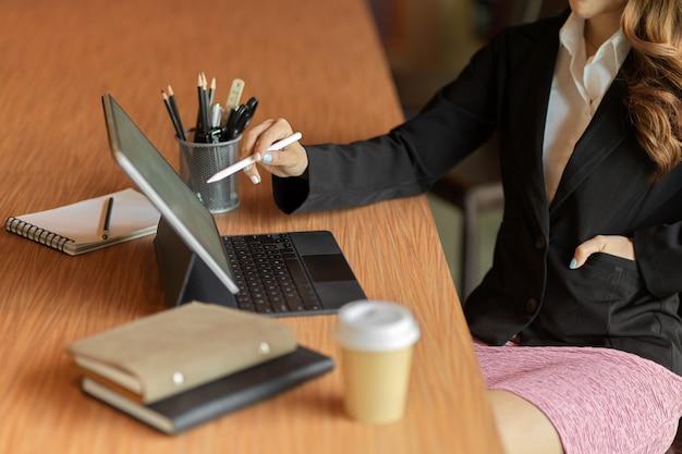 Обрезанный снимок деловой женщины-работницы, использующей стилус, работающей на смарт-планшете с расписаниями