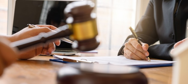 사업 사람들과 변호사 또는 판사 팀이 서명 계약, 법률 개념, 조언, 법률 서비스를 논의하는 자른 샷.