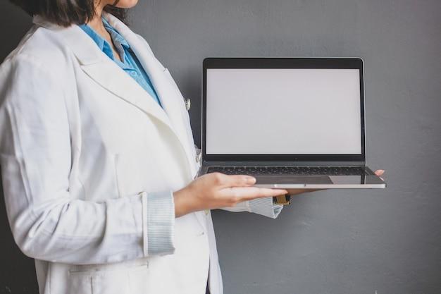 회색 배경에 빈 흰색 화면 노트북을 들고 사업 여자의 자른 된 샷