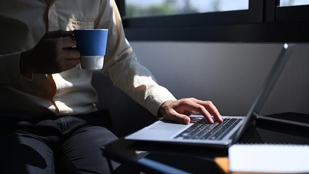 Обрезанный снимок бизнесмена, держащего чашку кофе и проверки электронной почты на портативном компьютере.