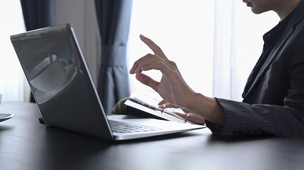 Обрезанный снимок бизнесмена с помощью портативного компьютера.