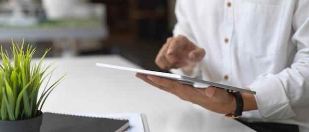 Обрезанный снимок бизнесмена, работающего над своим проектом с планшетом в офисной комнате