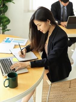 사무실 방에서 노트북과 편지지로 그녀의 작업에 집중하는 사업가의 자른 샷