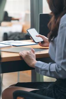 책상 사무실, 제품 디스플레이 또는 그래픽 디자인을 위한 빈 화면에 앉아 스마트폰을 사용하는 사업가 손의 자른 사진.