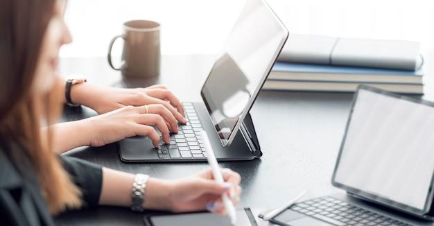 Обрезанный снимок руки бизнесвумен, работающих на планшетном компьютере, сидя за офисным столом, панорамный вид.