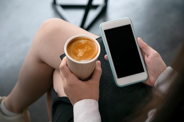 Обрезанный снимок бизнес-леди, держа смартфон пустой экран и чашку кофе, сидя в офисной комнате.