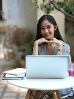 Обрезанный снимок деловой женщины, улыбаясь в камеру, работая с ноутбуком в кафе