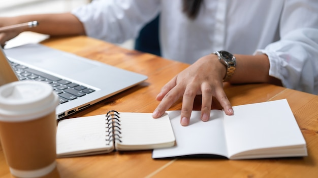 Обрезанный снимок бизнес-леди, работающей над своим проектом, используя ноутбук в рабочей области