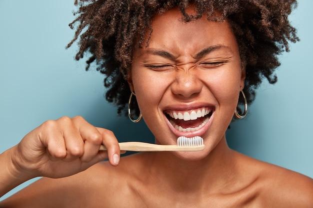 쾌활한 기쁜 어두운 피부를 가진 숙녀의 자른 샷은 하얀 치아를 보여주고, 표정을 즐겼고, 아침에 기분이 좋고, 치과 의사 방문을 준비하고, 파란색 벽에 고립 된 반 알몸으로 서 있습니다.