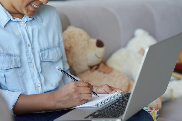 소파에 앉아 노트북을 사용하는 쾌활한 십대 여학생의 자른 샷