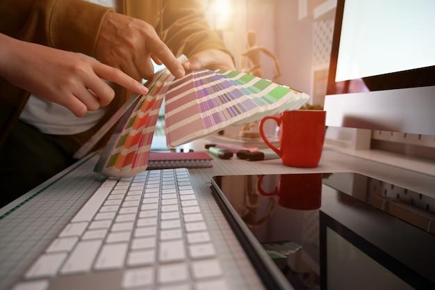 색상 선택 및 색상 견본 작업을하는 창의적인 그래픽 디자이너의 자른 샷