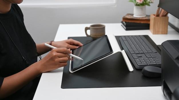 Обрезанный снимок творческой женщины, держащей стилус и работающей с цифровым планшетом за офисным столом.
