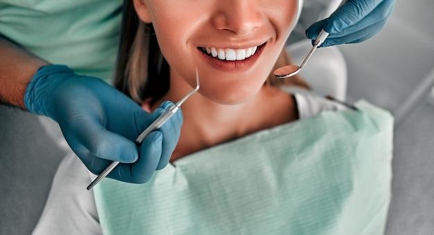 아름 다운 여성 고객의 치아를 검사 하는 치과 의사의 자른된 샷. 건강한 치아 개념입니다.
