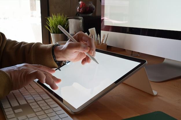 Обрезанный снимок дизайнера с помощью графического планшета при работе с компьютером в студии или офисе