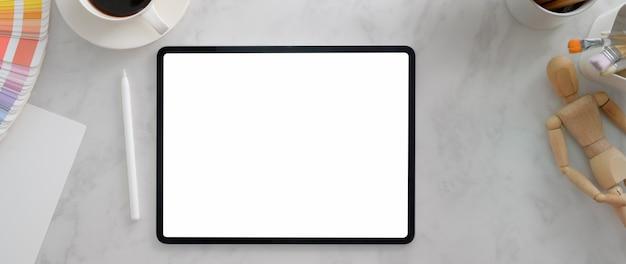 Кадрированный снимок дизайнерского рабочего пространства с планшетом, дизайнерскими принадлежностями и кофейной чашкой