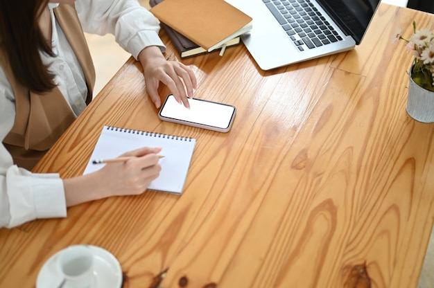 Обрезанный снимок девушки-дизайнера, пишущей свой проект на ноутбуке, используя смартфон с белым экраном
