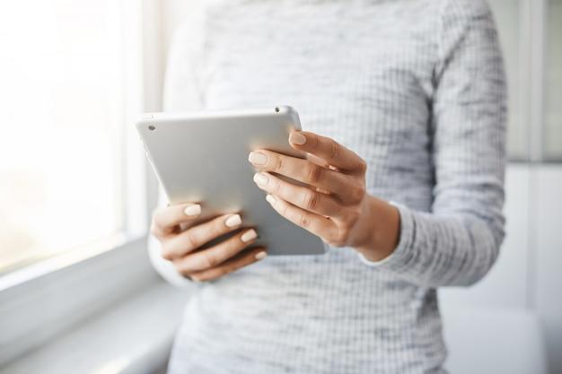 雇用主が窓の近くに立っている、デジタルタブレットを持っている、ソーシャルメディアでニュースを読んでいる、メールボックスをチェックしている、仕事中に忙しいのを切り取ったショット。美しい景色を撮りたい女性