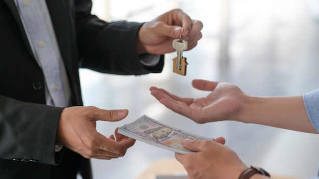 買い手と売り手の間のドルと家の鍵の交換のトリミングされたショット。