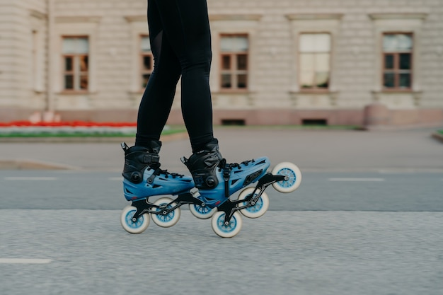 Обрезанный снимок безликой женщины, которая носит роликовые коньки для езды по дороге, увлекается хобби на свежем воздухе, ведет активный образ жизни, пробует новые ролики после покупки. людское хобби и досуг на свежем воздухе