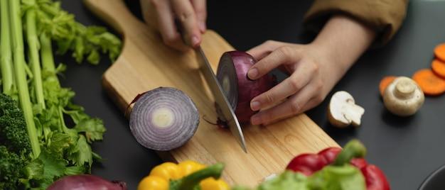 チョッピングブロックに新鮮な赤玉ねぎを切る女性料理人のショットをトリミング