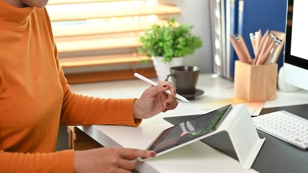 クリエイティブなワークスペースに座ってデジタルテーブルを使用して女性デザイナーのトリミングされたショット。