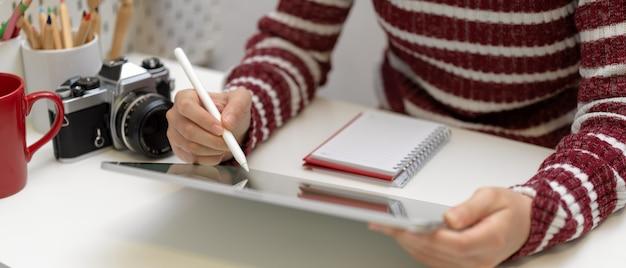 카메라와 용품 흰색 테이블에 스타일러스와 디지털 테이블에서 작업하는 여성 디자이너의 자른 샷