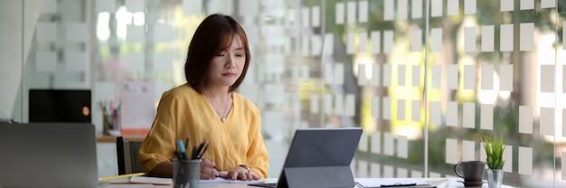ガラス壁のオフィスでの彼女の仕事に焦点を当てた女性起業家のショットをトリミング