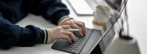 흰색 작업 테이블에 디지털 태블릿에 입력하는 여성 프리랜서의 자른 샷