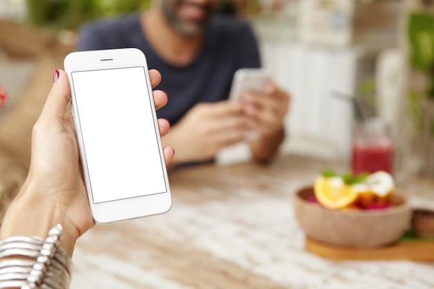 朝食時にアプリをオンラインで使用して、タッチパッド付きの携帯電話を持っている女性の手のショットをトリミングしました。電子メールでメッセージを読んでいる女性、カフェで無料のインターネット接続を楽しんでいます。