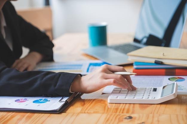 財務報告書を確認しながら電卓に取り組んでいるビジネスカジュアルで女性の手のショットをトリミング