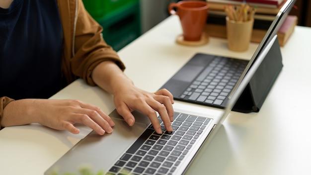 Обрезанный снимок женской руки, печатающей на клавиатуре ноутбука на офисном столе с другим ноутбуком, книгами и канцелярскими принадлежностями