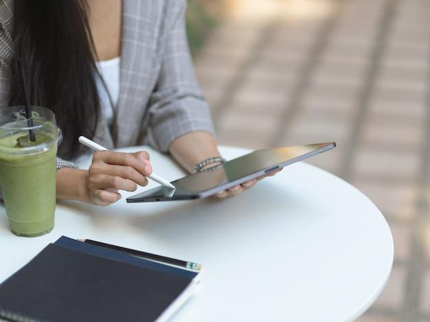 Обрезанный снимок женской руки с помощью цифрового планшета на журнальном столике с ноутбуком и напитком